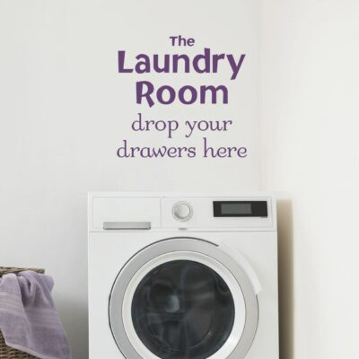The laundry room drop your drawers here vinyl saying in black on a white wall over a washing machine with a basket with a towel draped over the side