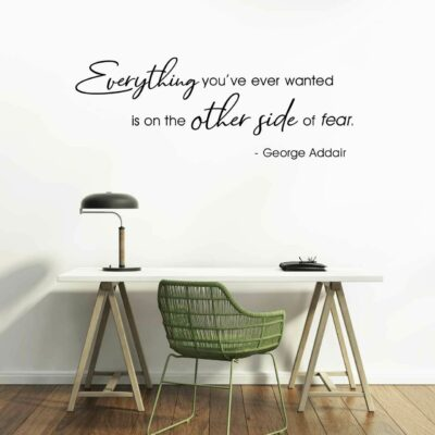 """""""Everything you've ever wanted is on the other side of fear. - George Addair"""" written in black vinyl lettering applied to a white wall over a work table containing a lamp and with a green chair pushed underneath"""