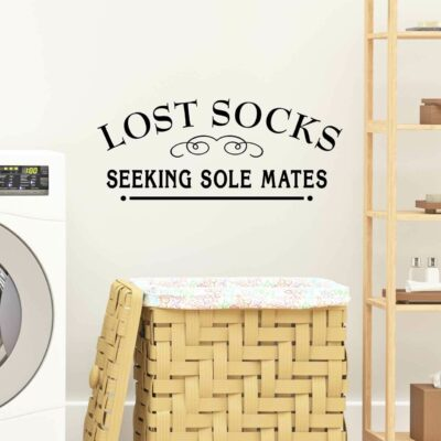 """""""Lost Socks Seeking Sole Mates"""" written in black vinyl lettering applied to a white wall over a laundry basket and between a washing machine and a standing shelf"""