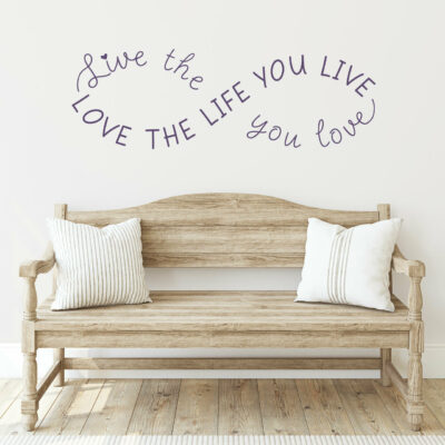 Live the life you love love the life you live in violet vinyl lettering on a white wall over a wooden bench