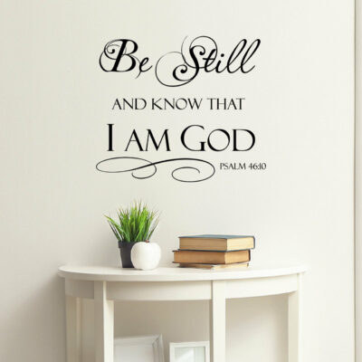 Be still and know that i am god vinyl lettering in black on a white wall over a console table with books and a plant on it