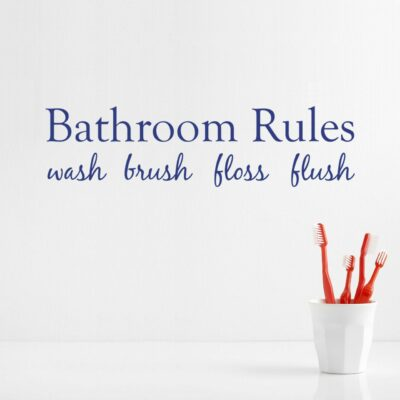 Bathroom rules wash brush floss flush written in navy colored vinyl lettering on a white wall over some red toothbrushes