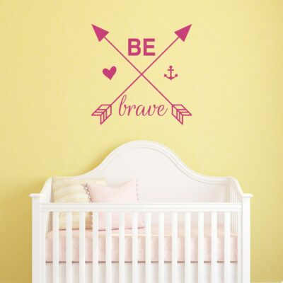"""""""Be brave"""" with arrows, heart and anchor in hot pink vinyl on a yellow wall over white crib"""