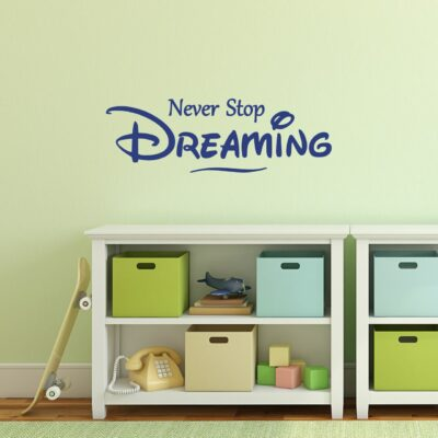 Never stop dreaming vinyl lettering layout in blue applied to a key lime green wall over a white toy shelf with a skateboard leaning against it.