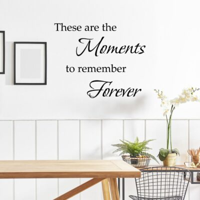 These are the moments to remember vinyl lettering layout in black on a white wall to the right of a black picture frame over a wood table