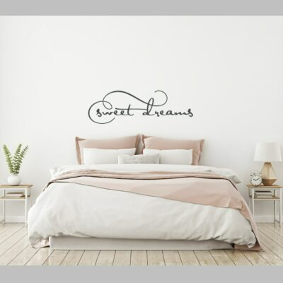 Sweet dreams vinyl lettering layout in charcoal grey on a white wall over a king sized bed with white and soft pink accents and two nightstand tables