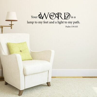 """""""Your word is a lamp to my feet and a light to my path. - Psalm 119:105"""" in black vinyl lettering applied to a beige wall over a reading chair and next to a lamp"""