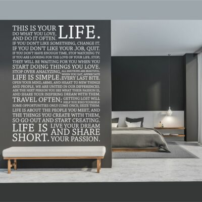 The Holstee Manifesto in white vinyl lettering on a dark grey background over a white cloth bench in a bedroom with a bed and nightstand to the right