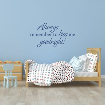 Always remember to kiss me goodnight! written in blue vinyl lettering on a light blue wall over a toddler bed with a small light blue chair on the left