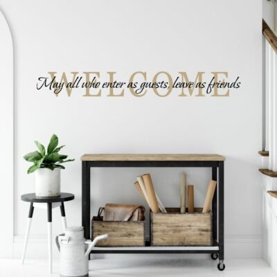 Welcome may all who enter as guests leave as friends written in burlap and black  colored vinyl lettering on a white wall in an entry over a rolling cabinet with a plant on a stand to the left