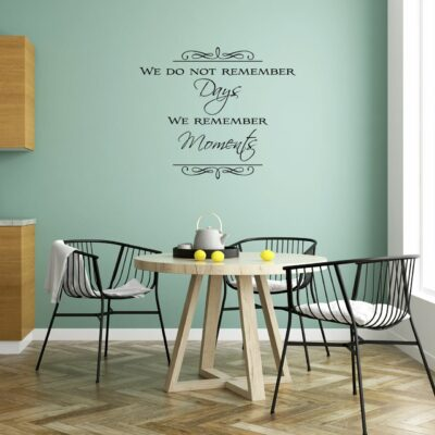 We do not remember days we remember moments written in mixed fonts in black vinyl lettering on a light green wall over a small dining table