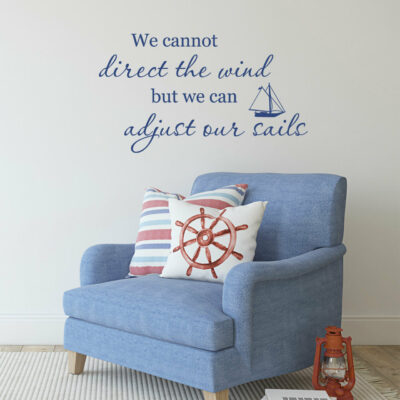 We cannot direct the wind but we can adjust our sails vinyl lettering in navy blue on a white wall over a blue armchair