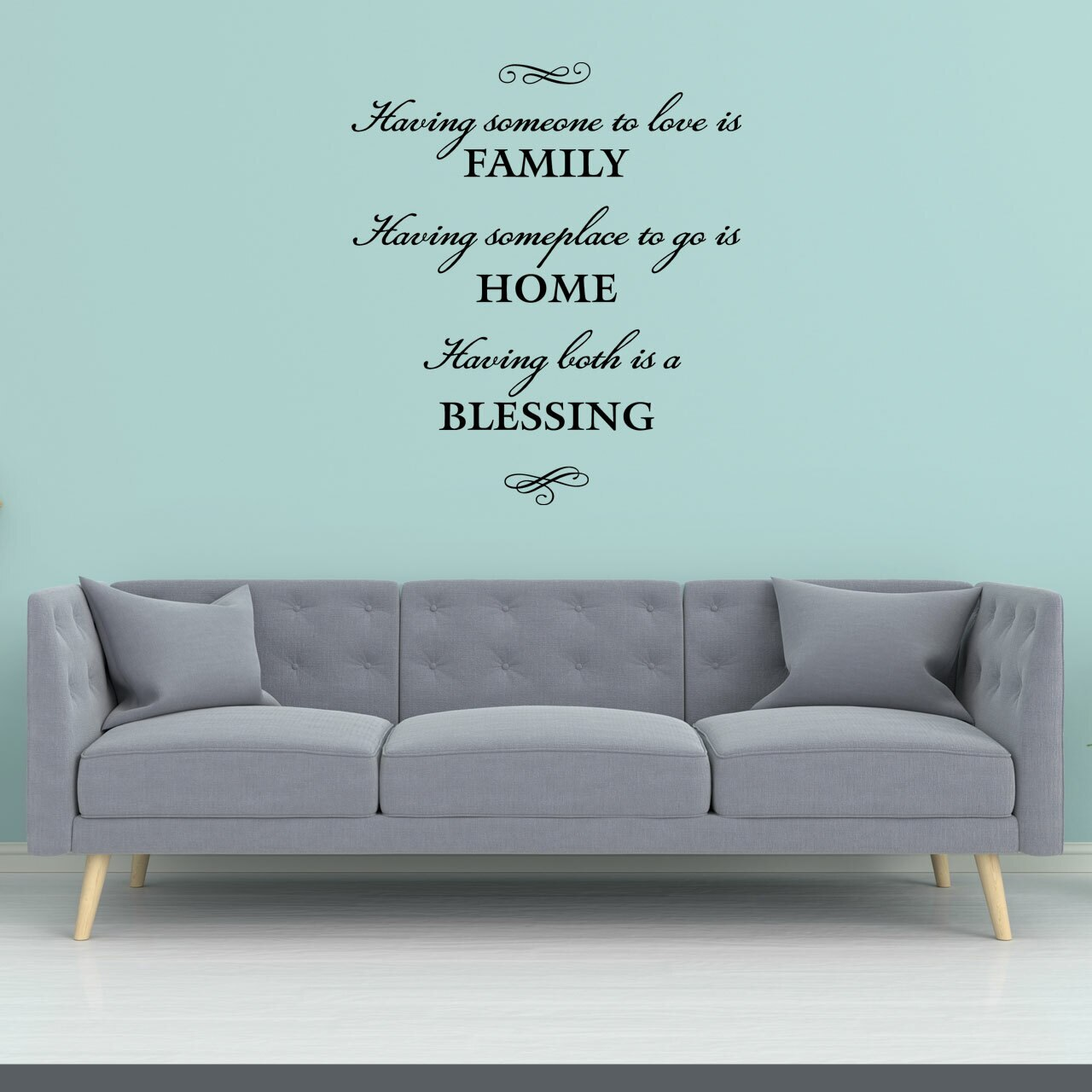 Having someone to love is family having somewhere to go is home having both is a blessing written in black vinyl lettering on a teal wall over a grey couch