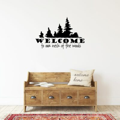 Welcome to our neck of the woods written in black vinyl lettering on a white wall over a bench