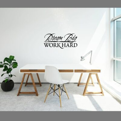 Dream big work hard written in black vinyl lettering to a white wall over a work table flanked by a plant and a window