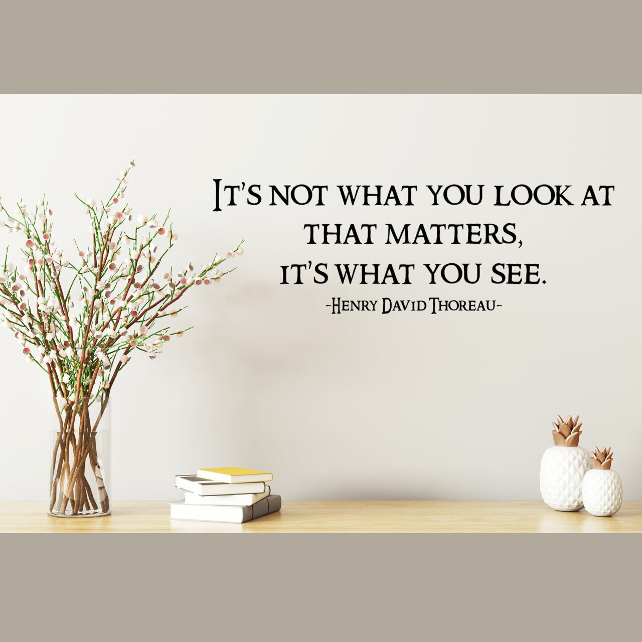 It's not what you look at it's what you see -Henry David Thoreau written in black vinyl lettering on a white wall over flowers in a vase, books, and decorative ceramic pieces
