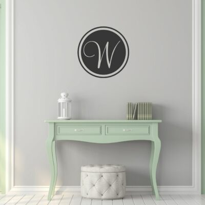 Single letter circular monogram with the letter W in charcoal grey vinyl applied to a wall over a pale green console table