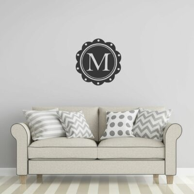 Charcoal grey single letter circular monogram with scalloped edges and the letter M in the middle in vinyl applied to a wall over a beige couch