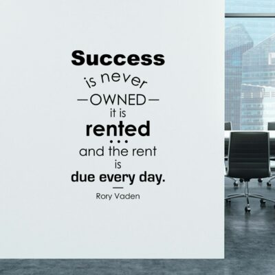 Success is never owned it is rented and the rent is due every day. -Rory Vaden  in black vinyl lettering on a white wall in a business