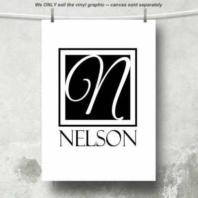 Single letter monogram in a square with the letter N centered over the last name NELSON in black vinyl on a white canvas hanging from a cord