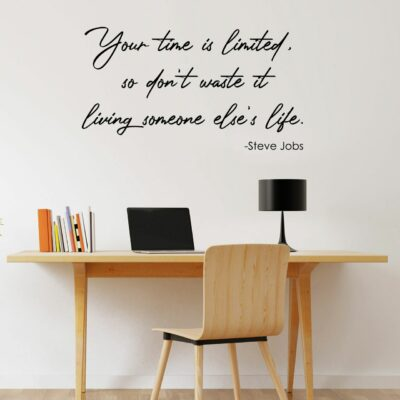 Your time is limited so don't waste it living someone else's life. -Steve Jobs written in a black vinyl lettering on a white wall over a desk with books lamp and computer