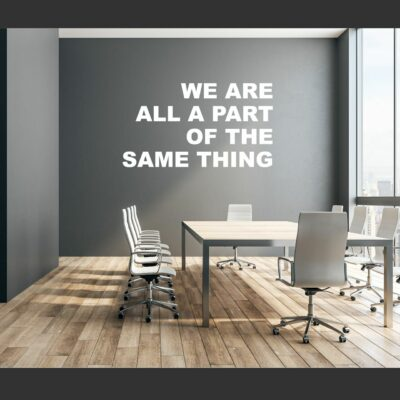 We Are All A Part Of The Same Thing written in white vinyl lettering on a grey wall in a conference room above a conference table surrounded by chairs