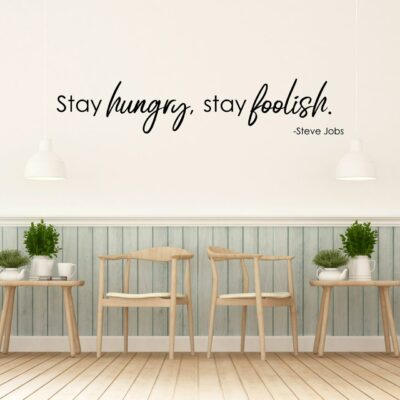 Stay hungry, stay foolish. - Steve Jobs written in black vinyl lettering applied to a white wall over two chairs and two small side tables