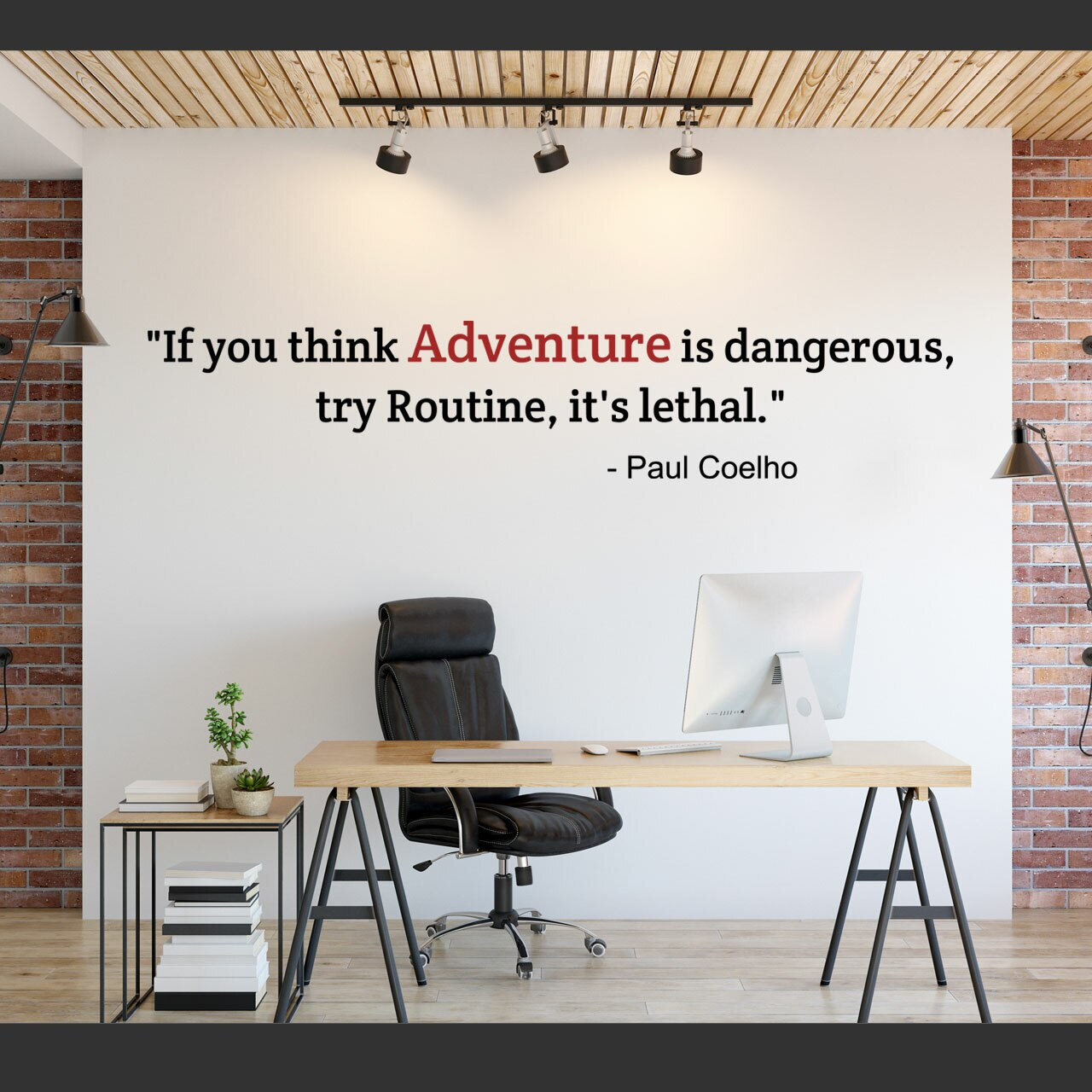 If you think Adventure is dangerous, try routine, it's lethal -Paul Coelho written in black vinyl lettering and the word Adventure in red vinyl lettering on a white wall over a desk