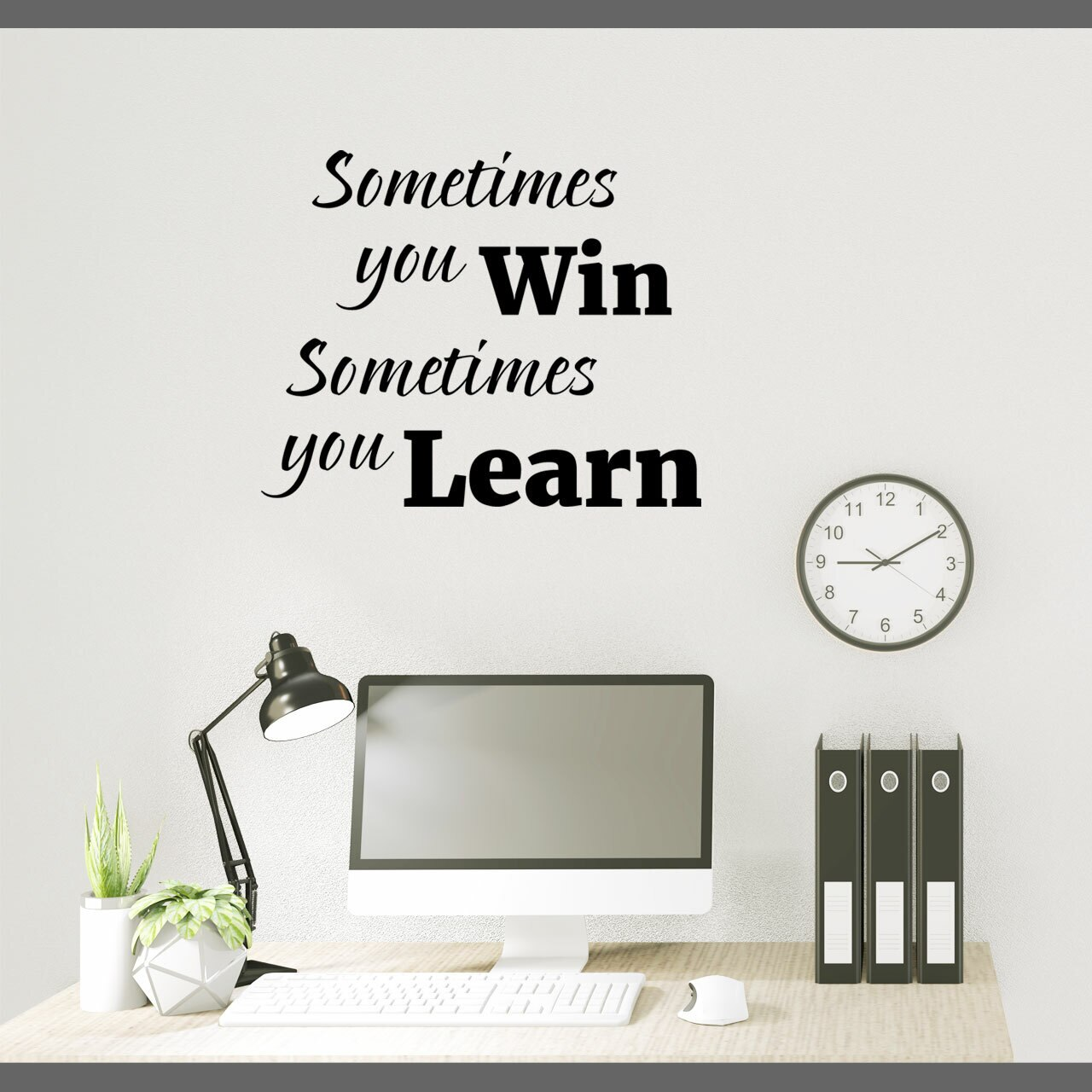 Sometimes you win sometimes you learn written on multiple lines in black vinyl lettering on a white wall over a computer desk