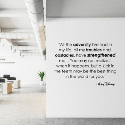 All the adversity I've had in my life, all my troubles and obstacles, have strengthened me...You may not realize it when it happens, but a kick in the teeth may be the best thing in the world for you. -Walt Disney written on multiple lines in black vinyl lettering on a white wall in an office environment