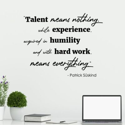 Talent means nothing. While experience acquired in humility with hard work means everything. -Patrick Suskind written in mixed fonts on multiple lines in black vinyl lettering on a white wall over a computer desk