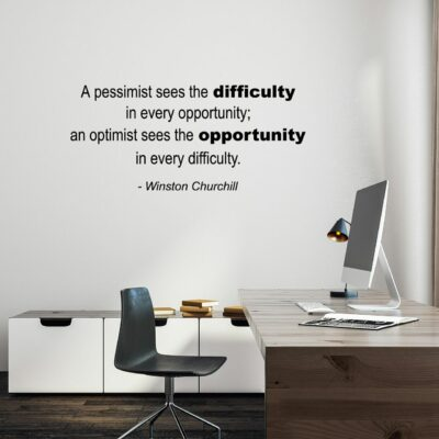 A pessimist sees the difficulty in every opportunity. An optimist see the opportunity in every difficulty. -Winston Churchill written on multiple lines in black vinyl lettering on a white wall over a computer desk