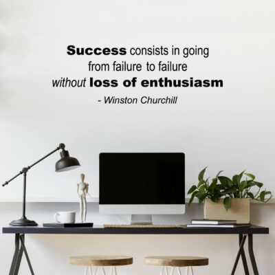 """""""Success consists of going from failure to failure without loss of enthusiasm"""" - Winston Churchill written in black vinyl lettering on multiple lines on a white wall over a computer screen on a desk"""