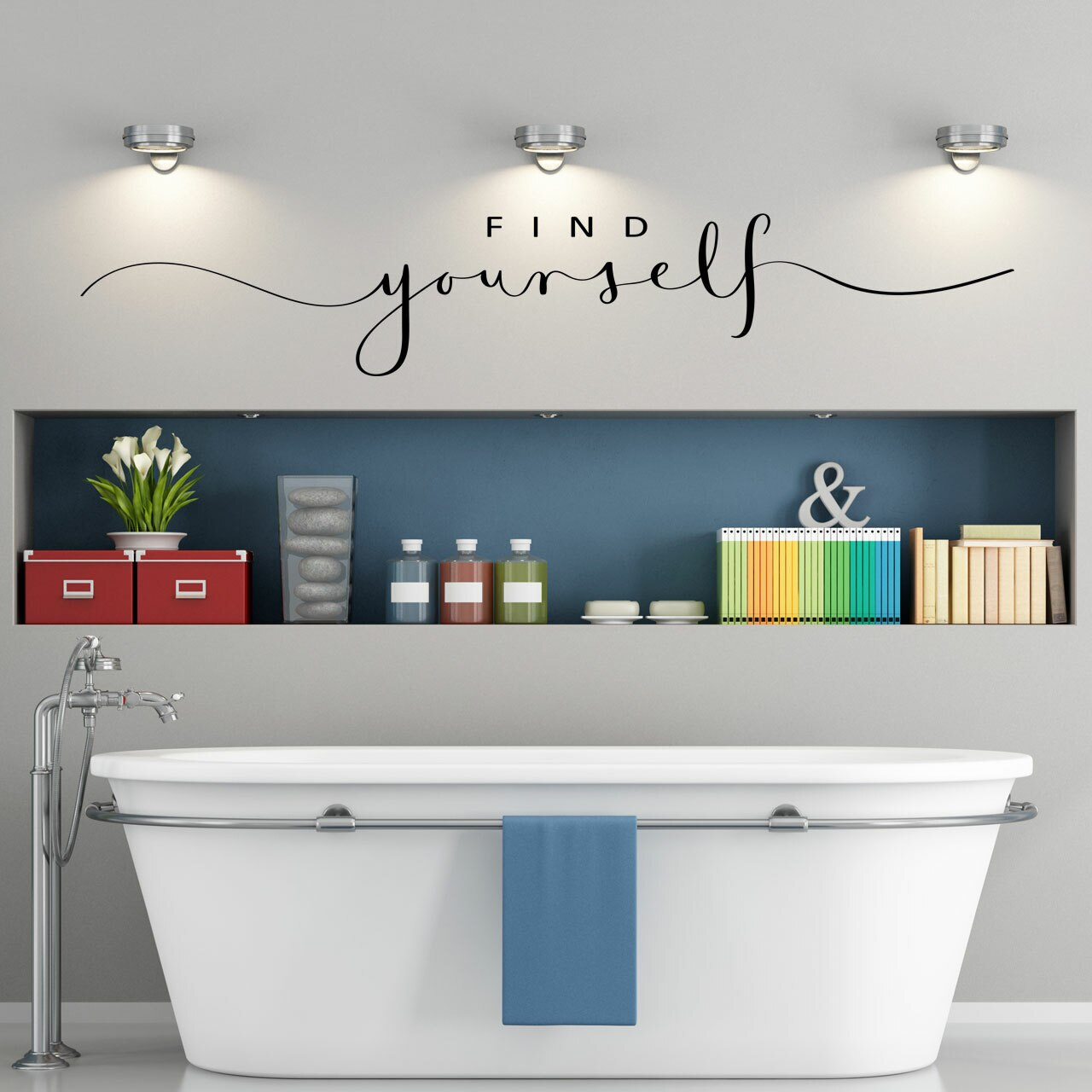"""""""FIND yourself"""" written in mixed fonts in black vinyl lettering on a light grey wall over a white bathtub and an inset shelf with various colorful items"""