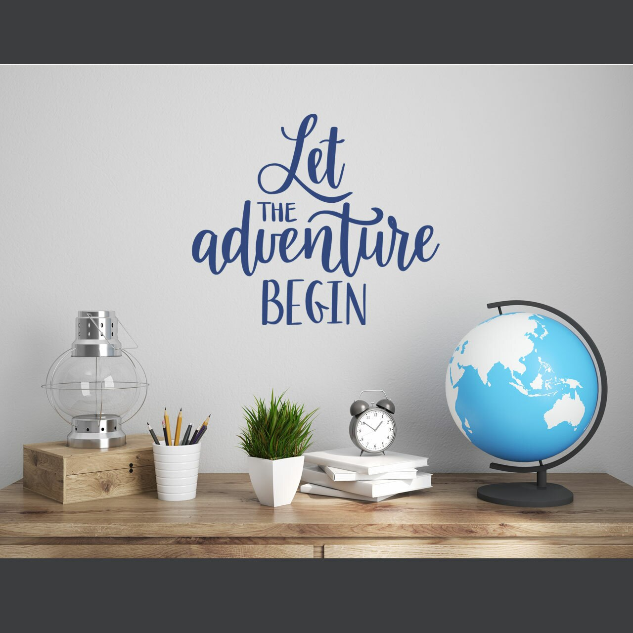 """""""Let the adventure begin"""" written in blue vinyl lettering in mixed fonts stacked in a vertical arrangement on a white wall over a desk with a globe, lantern, pencil cup, a plant,  some books stacked, and a clock"""