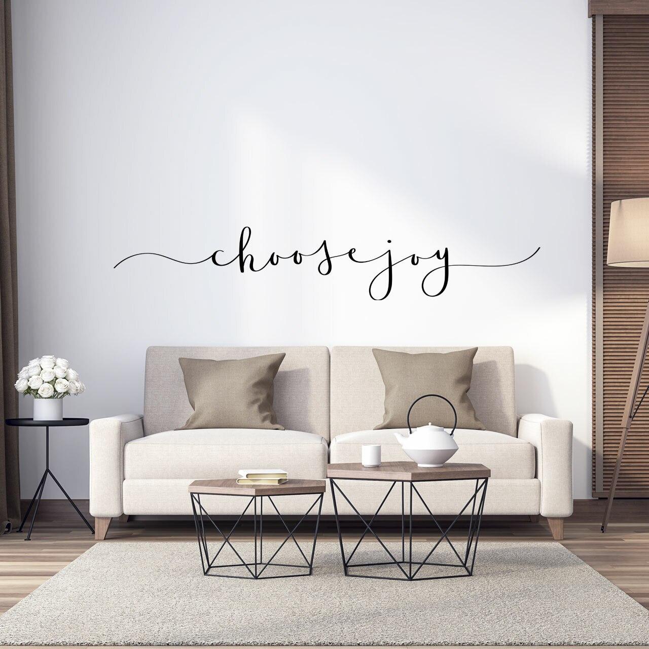 """choose joy"" written in a flowing script font in black vinyl lettering on a white wall over a beige couch"