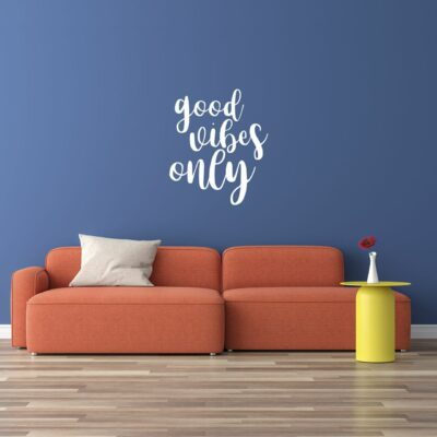 """""""good vibes only"""" written in a youthful script font in white vinyl lettering on a blue wall over a pale orange couch"""
