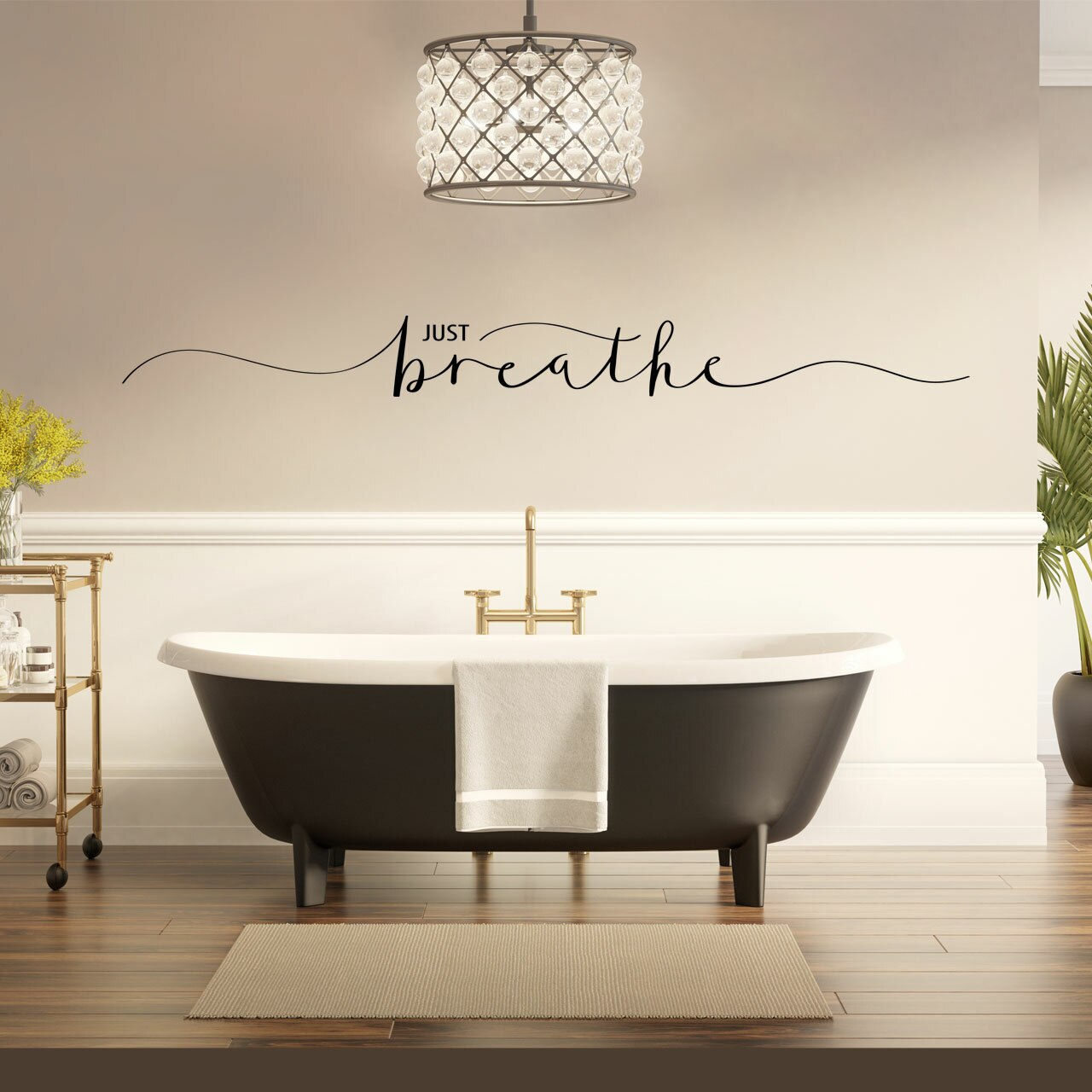"""""""JUST breathe"""" written in black vinyl lettering in mixed fonts on a beige wall in a bathroom over a dark brown bathtub"""