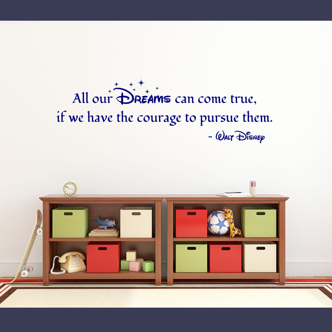 """""""All our Dreams can come true if we have the courage to pursue them."""" -Walt Disney written in blue vinyl lettering on a white wall over some bookcases."""