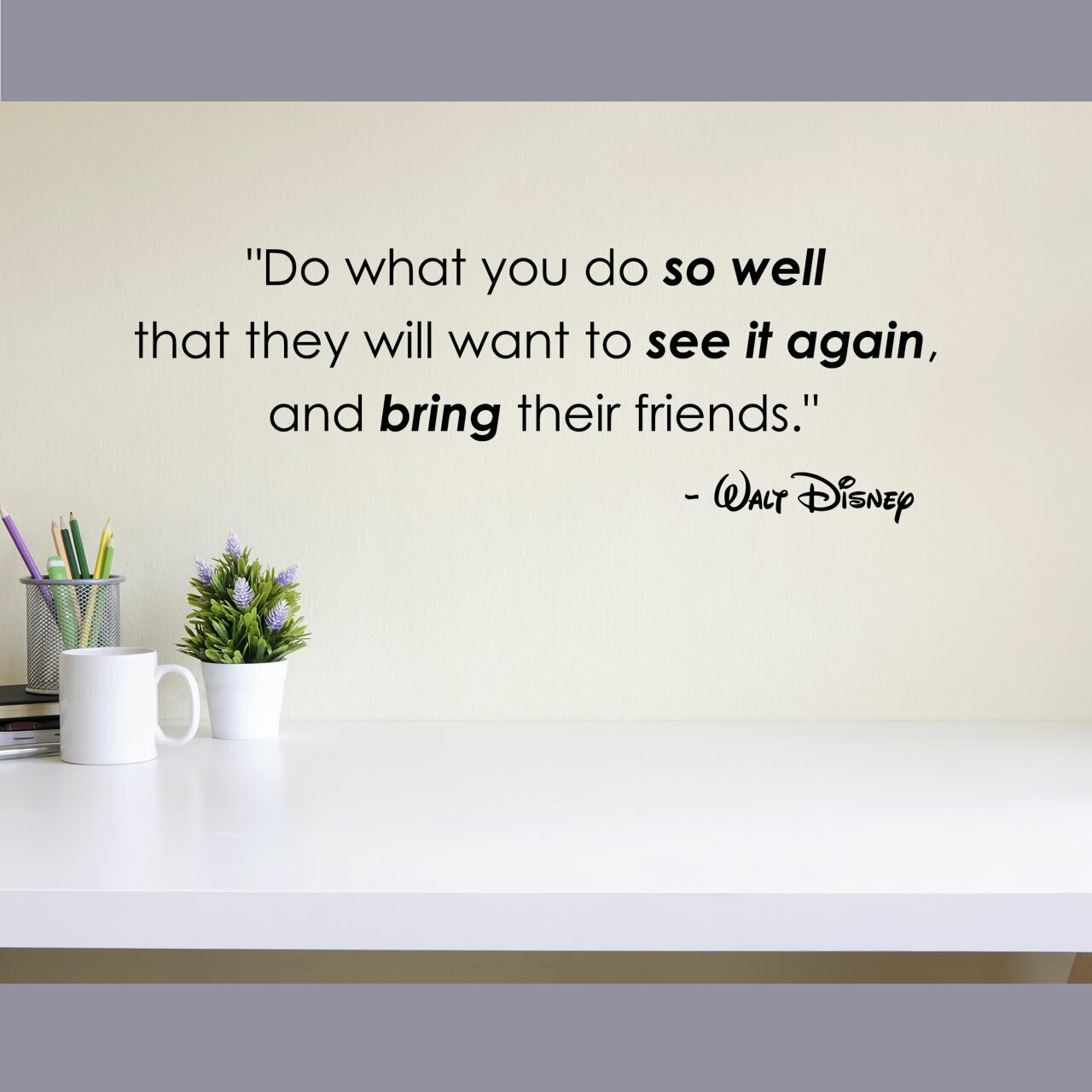 """""""Do what you do so well that they will want to see it again and bring their friends"""" -Walt Disney written in black vinyl lettering  applied to a beige wall to the right of a coffee cup, a basket with colored pencils and a potted plant"""