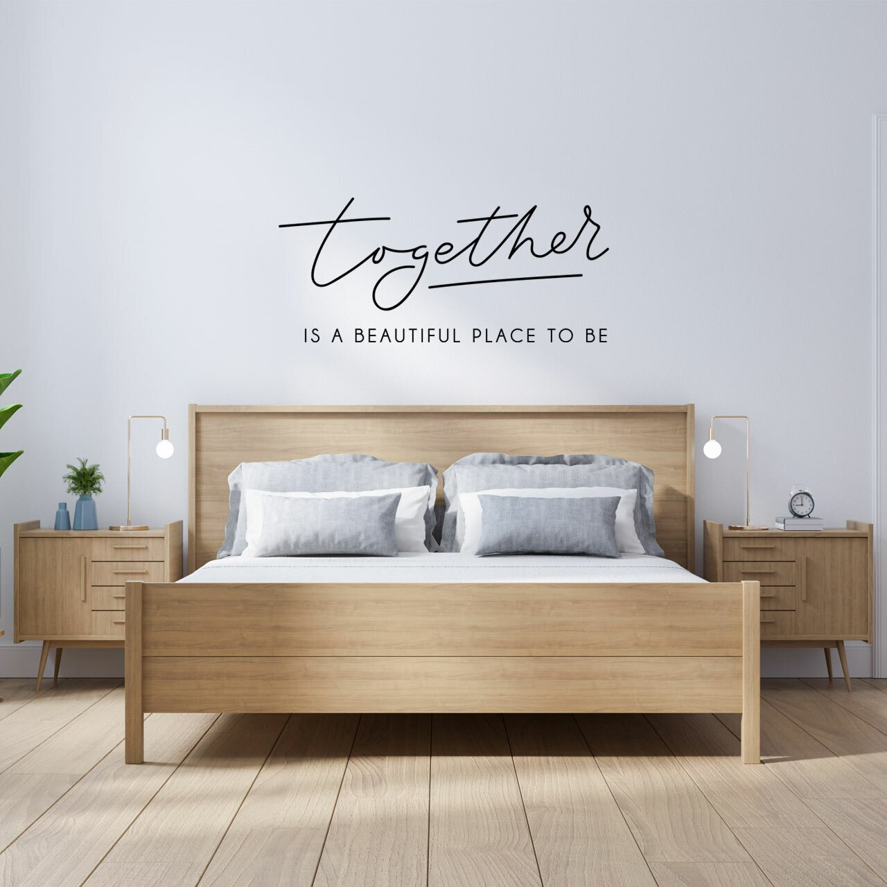 """""""Together is a beautiful place to be"""" written in black vinyl lettering in two different fonts on a white wall over a light colored wooden headboard"""
