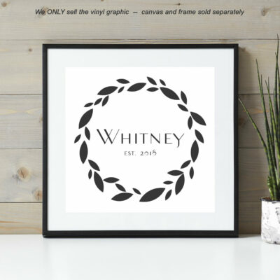 Leaf wreath around last name and year established on a white canvas with a black frame leaning against a wall