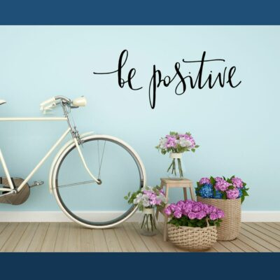"""""""be positive"""" written in black vinyl lettering on a light blue wall over some flowers and a white bicycle"""
