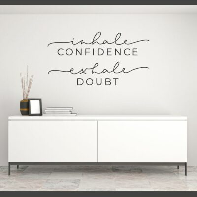 Inhale Confidence Exhale Doubt written in mixed fonts on four lines in black vinyl lettering applied to a white wall over a console table