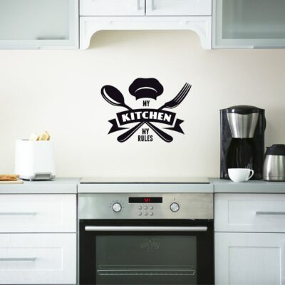 """""""My Rules My Kitchen"""" written in an artistic way including the words, a chef's hat, a spoon and fork, and a banner in black vinyl lettering applied to a white wall over a stove in a kitchen"""