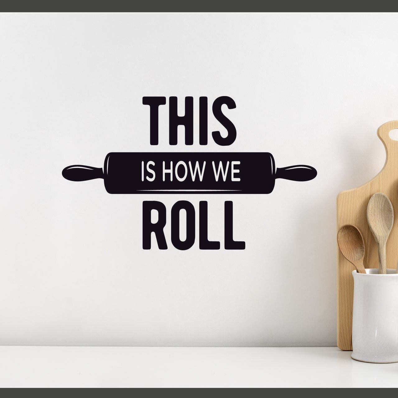 """""""This is how we roll"""" written on 3 lines with a rolling pin on the middle line in black vinyl lettering applied to a white wall over a kitchen counter with some kitchen utensils in a ceramic pot to the right"""
