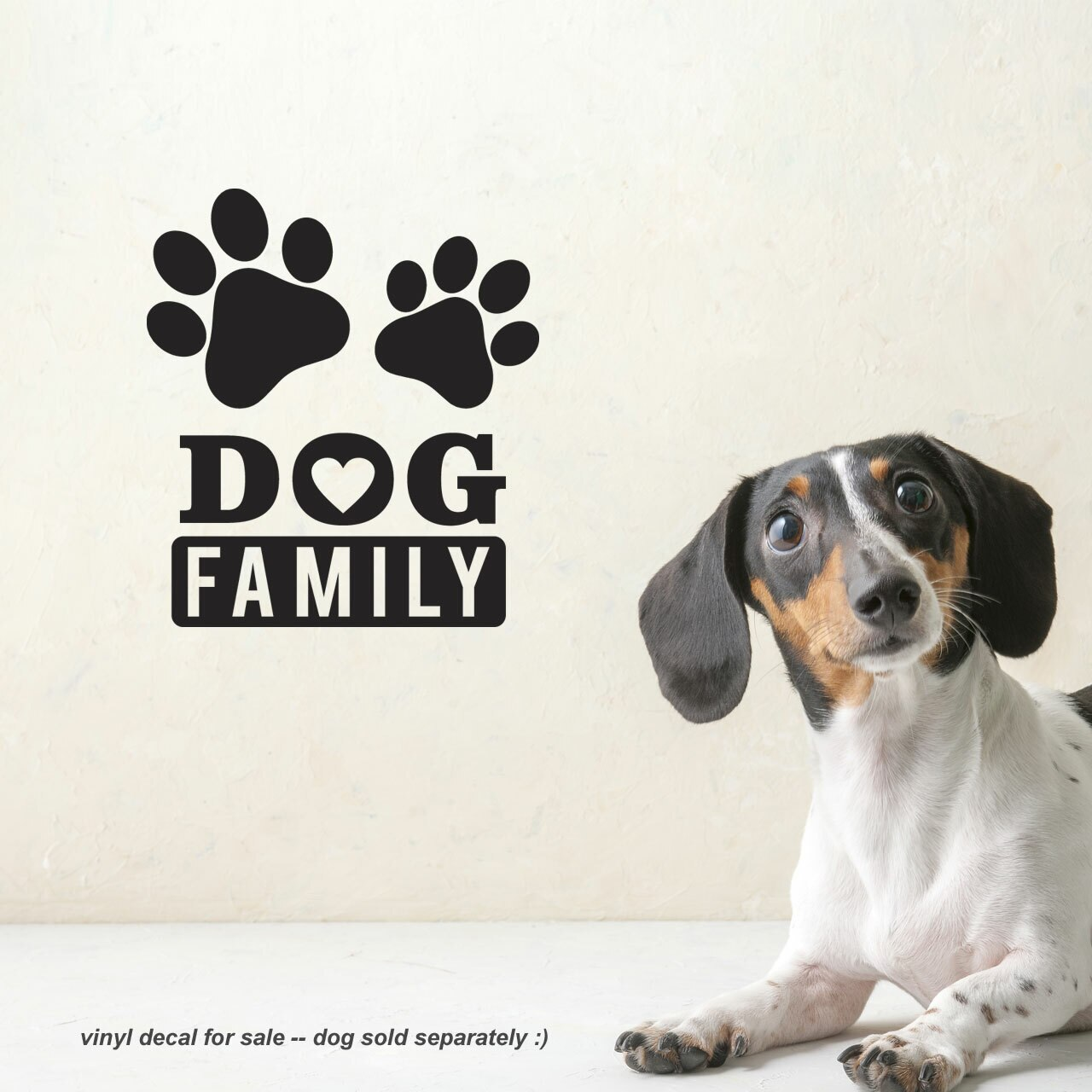 """Two paw-prints with the words """"Dog Family"""" written beneath in an artistic way in black vinyl applied to a white wall to the left of a small dog"""