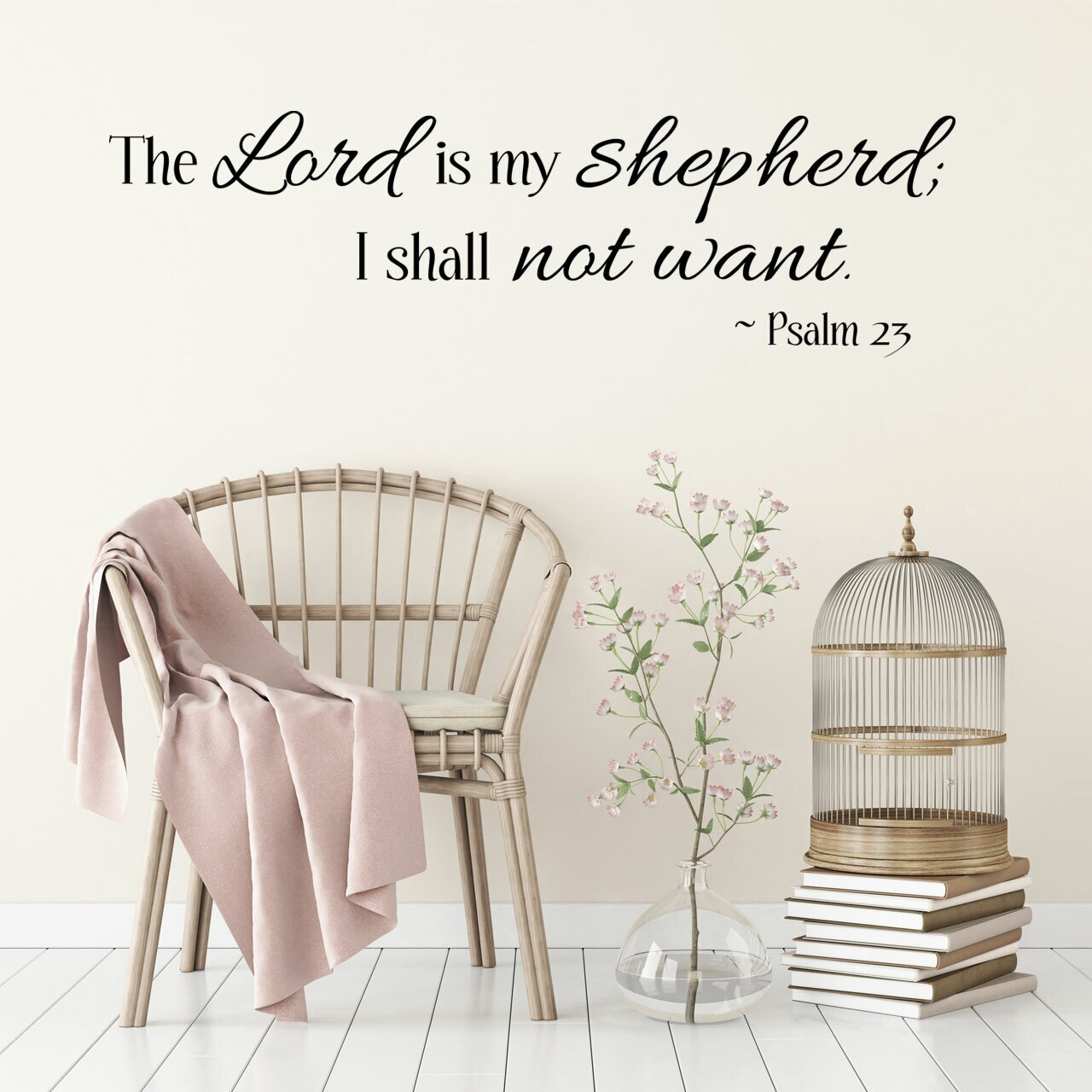 """""""The Lord is my shepherd; I shall not want. - Psalm 23"""" written in mixed fonts on two lines in black vinyl lettering applied to a white wall over a chair, a vase containing a branch and a birdcage on a stack of books"""