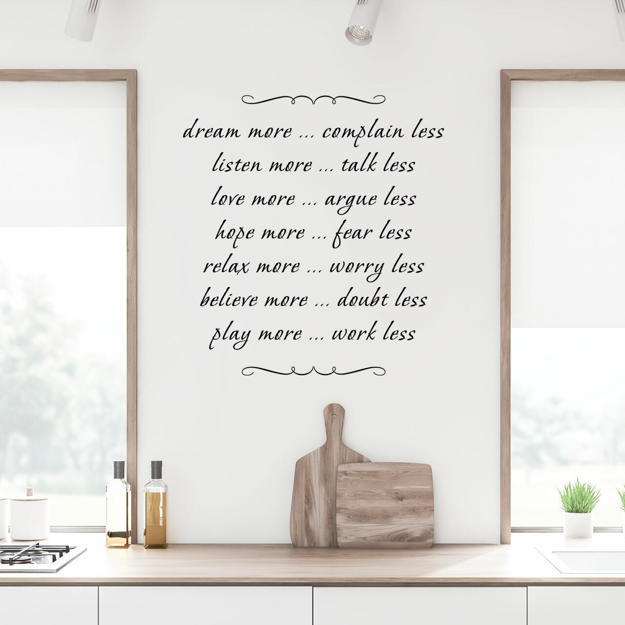 dream more complain less ... listen more talk less ... love more argue less ... hope more fear less ... relax more worry less ... believe more doubt less ... play more work less written in multiple lines with decorative scrolls on the top and bottom in black vinyl lettering applied to a white kitchen wall over a counter holding two cutting boards