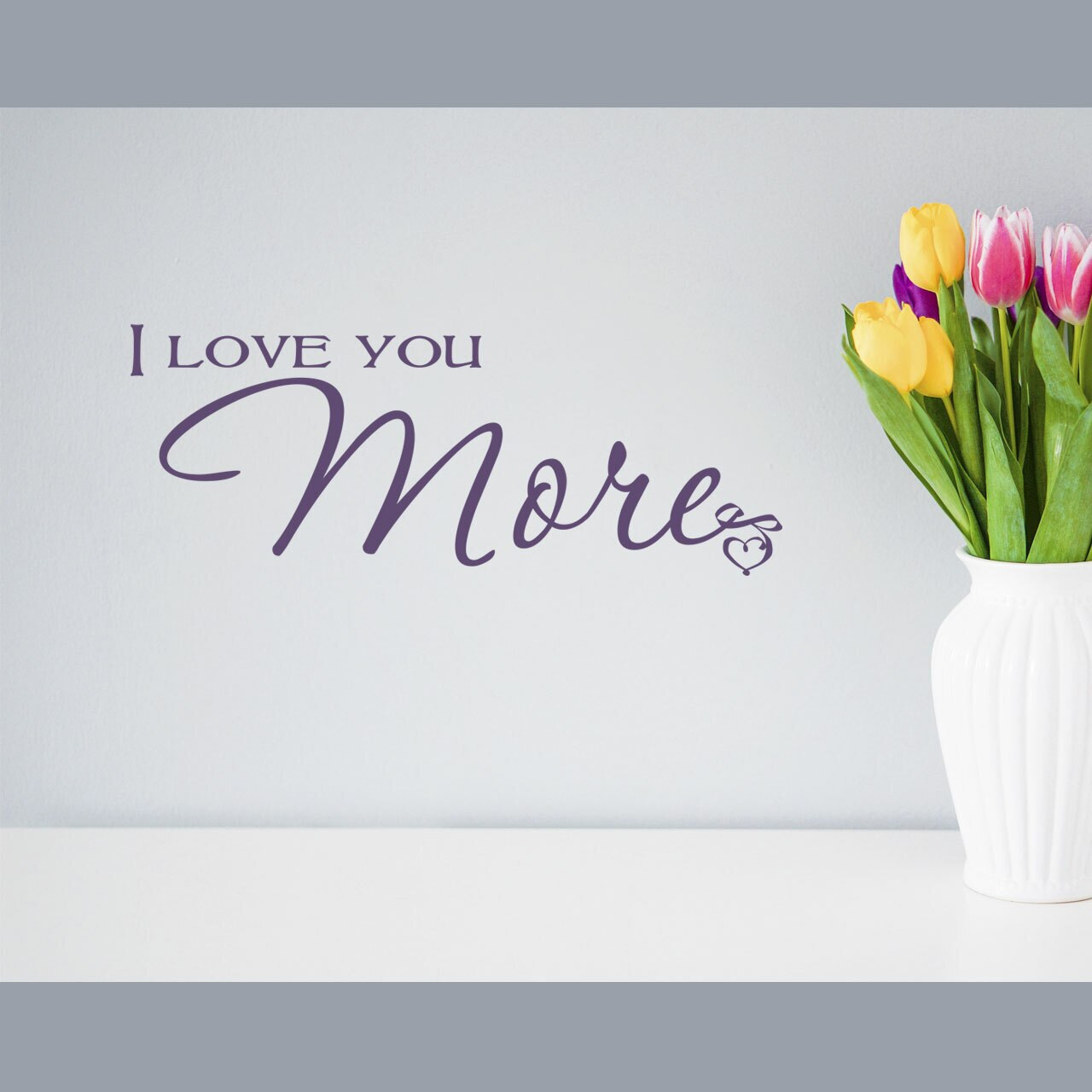 """""""I Love You More"""" written on two lines in mixed fonts in violet vinyl lettering applied to a white wall to the left of a vase holding tulips"""